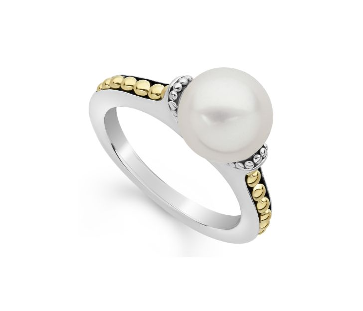 Front view of ring. A 9mm pearl center is hugged on either side by sterling islver beaded bar prongs. The silver shank is accented by yellow gold beaded details studded in channel like setting with a black backdrop.