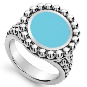 Top view looking down. A light blue ceramic center is halo by sterling silver beaded details. It is attached to a tapered sterling silver shank with additional beaded details decorating the shoulders of the ring.