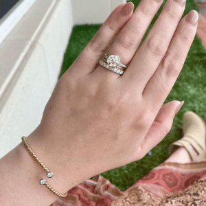 stack of three diamond rings on ring finger and gold rope bangle with diamonds on wrist