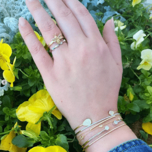 gold, silver and diamond bracelets and rings on model with floral background