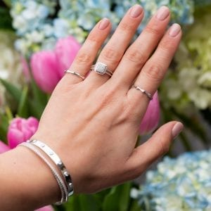 woman holding hand infront of flowers, wearing silver and white gold diamond rings and bracelets