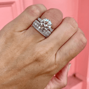 2 diamond rings on hand with pink background