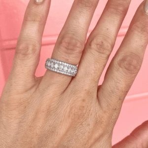 diamond ring on hand with pink background