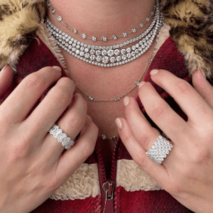 2 diamond rings worn on ring finger and multiple diamond necklaces worn on neck