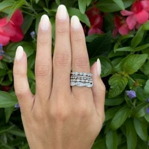 white gold diamond band rings stacked on womens pointer finger hand in front of tree