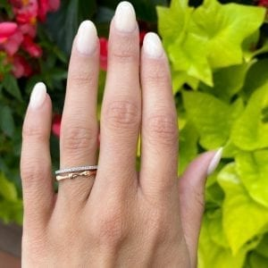 rose gold bamboo gold band ring stacked with white gold pave diamond band on top on womens left hand ring finger in front of leaves