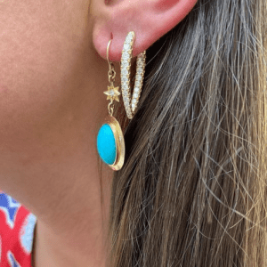 gold and turquoise drop earrings and gold diamond hoop earring on model