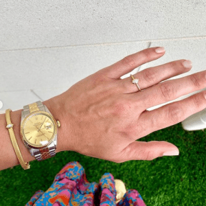 silver and gold watch and gold bracelet and ring on model