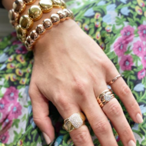 gold and diamond rings and gold bracelets on model with floral background