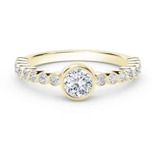 yellow gold diamond ring with bezel set center and smaller bezel set diamonds along the band