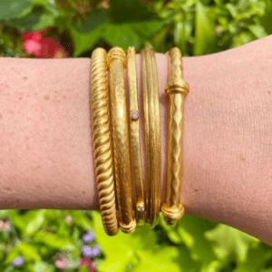 five gold bracelets on model's wrist