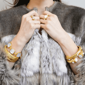gold bracelets and rings with white stones on model