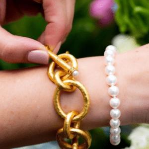 gold link bracelet and pearl bracelet on model