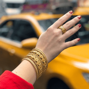 gold bracelets and ring on model with taxi in background