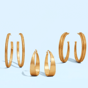 3 pairs of gold hoops earrings on blue background