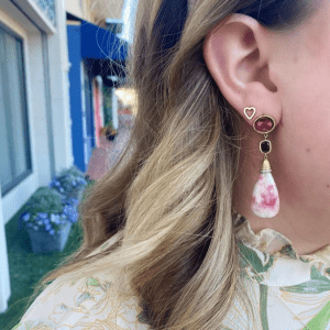 pink stone earring and gold heart earring on model