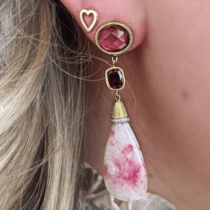 pink stone and gold earring and gold heart earring on model