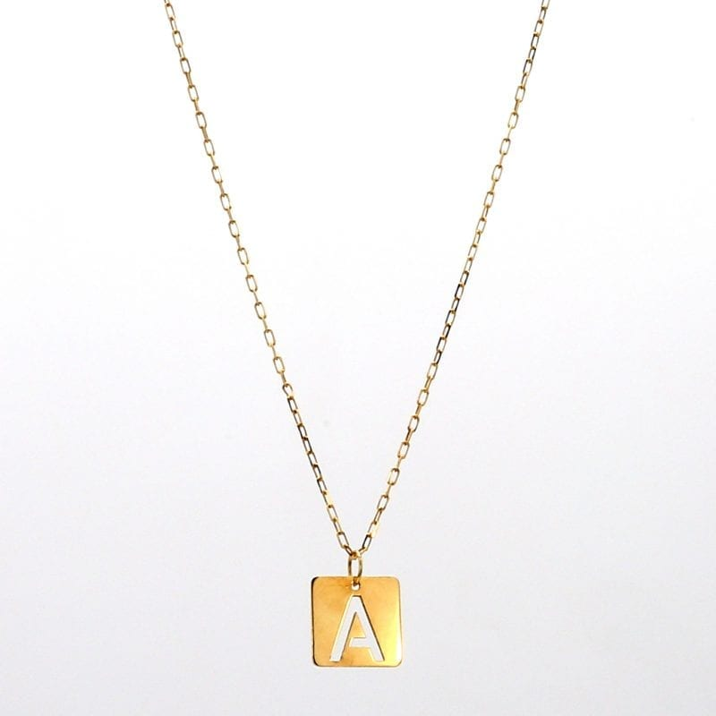 Yellow gold thin square tile pendant on chain with initial cut out in center of square suspended from thin cable chain