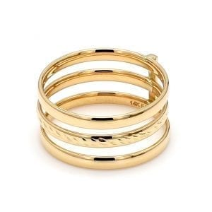45 degree angle of ring. Three bands of yellow gold are stacked with space in between each. The top and bottom band are polished and the center is textured. Secured in place by a vertical bar of yellow gold in the back.