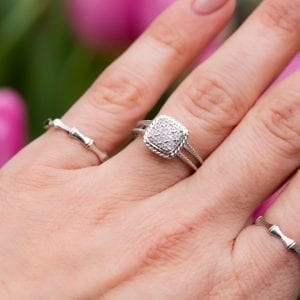 silver diamond cushion ring on ring finger of woman's hand