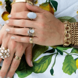 gold and colored stone rings and bracelets on model with floral backrgound