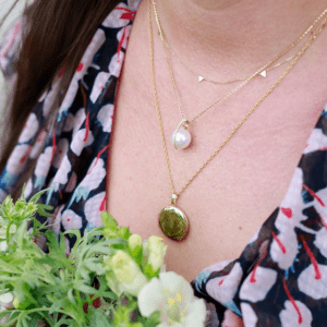 two gold necklaces and one gold and pearl necklace on model