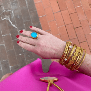 gold bracelets and gold and turquoise ring on model