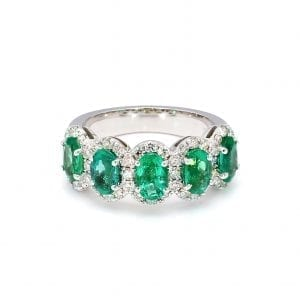 360 imaging of ring. A row of five oval cut emeralds are set along the front half of a simple white gold band with pave diamond halos around each.