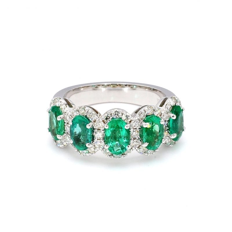 Front view of ring. A row of five oval cut emeralds are set along the front half of a simple white gold band with pave diamond halos around each.