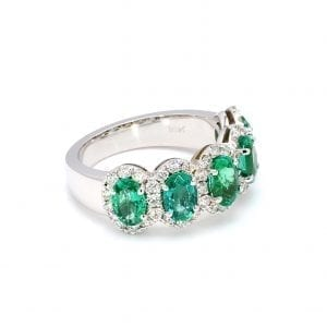45 degree angle of ring. A row of five oval cut emeralds are set along the front half of a simple white gold band with pave diamond halos around each.