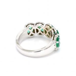 135 degree angle of ring. A simple white gold band leads to a five stone setting that holds five oval cut emeralds with pave diamond halos.