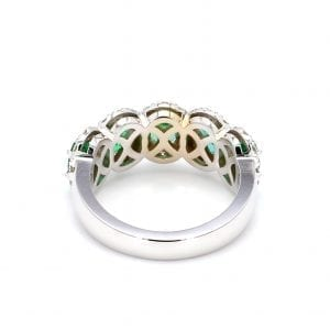 Back view of ring. A simple white gold band leads to a five stone setting that holds five oval cut emeralds with pave diamond halos.