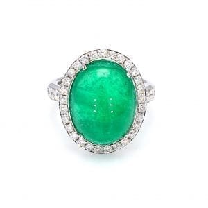 360 imaging of ring. A center cabochon emerald is haloed by round brilliant cut diamonds, with additional round brilliant cuts diamonds accenting half way down each side of a white gold shank.