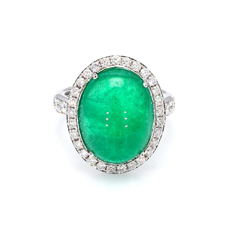 Front view of ring. A center cabochon emerald is haloed by round brilliant cut diamonds, with additional round brilliant cuts diamonds accenting half way down each side of a white gold shank.