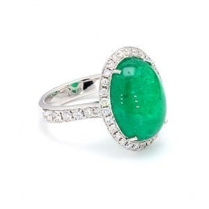 45 degree angle of ring. A center cabochon emerald is haloed by round brilliant cut diamonds, with additional round brilliant cuts diamonds accenting half way down each side of a white gold shank.