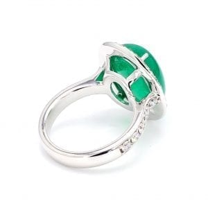 135 degree angle of ring. A white gold band with round brilliant cut diamonds accented halfway down each side leads to an oval setting that holds a cabochon emerald stone surrounded by a diamond halo.