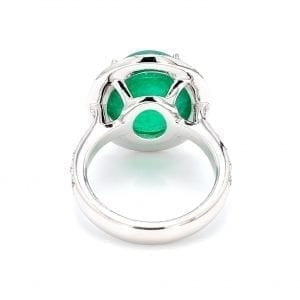 Back view of ring. A white gold band with round brilliant cut diamonds accented halfway down each side leads to an oval setting that holds a cabochon emerald stone surrounded by a diamond halo.