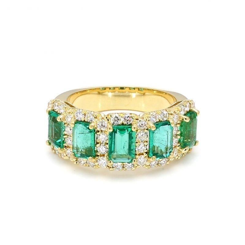 Front view of ring. Five emerald cut emeralds are surrounded by interlocking diamond halos along the front half of a thick yellow gold band.