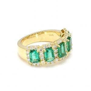 45 degree angle of ring. Five emerald cut emeralds are surrounded by interlocking diamond halos along the front half of a thick yellow gold band. Five emerald cut emeralds are surrounded by interlocking diamond halos along the front half of a thick yellow gold band.