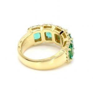 135 degree angle of ring. A tapered yellow gold band leads to a five stone setting that boasts five emerald cut emeralds with interlocking diamond halos along the front half.