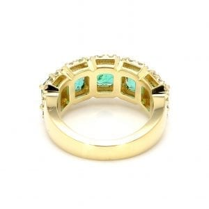 Back view of ring. A tapered yellow gold band leads to a five stone setting that boasts five emerald cut emeralds with interlocking diamond halos along the front half.