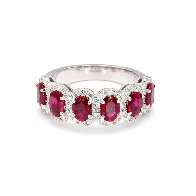Front view of ring. A row of six oval cut rubies band across the front half of a simple white gold band with interlocking pave diamond halos.