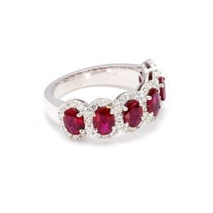 45 degree angle of ring. A row of six oval cut rubies band across the front half of a simple white gold band with interlocking pave diamond halos.