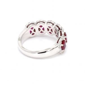 135 degree angle of ring. A simple white gold band leads to a six stone setting that holds six oval cut rubies with pave diamond halos surrounding each.