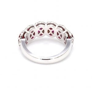 Back view of ring. A simple white gold band leads to a six stone setting that holds six oval cut rubies with pave diamond halos surrounding each.