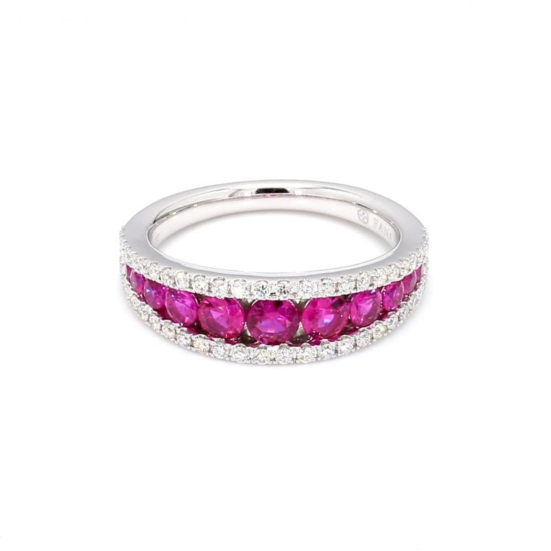 Front view of ring. A simple white gold band features tapered channel set rubies along the center with a band of pave diamonds framing the top and bottom.