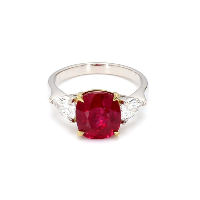 Front view of ring. A simple white gold band is decorated by a center cushion cut burma ruby set in 18k yellow gold with a pear cut diamond on either side.