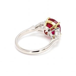 135 degree angle of ring. A simple white gold band leads to a three stone setting in white gold with a pear cut diamond on each side. The center stone setting is in 18kt yellow gold and holds a a center cushion cut ruby.