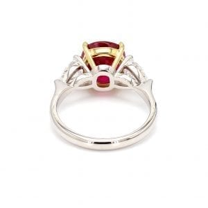 Back view of ring. A simple white gold band leads to a three stone setting in white gold with a pear cut diamond on each side. The center stone setting is in 18kt yellow gold and holds a a center cushion cut ruby.