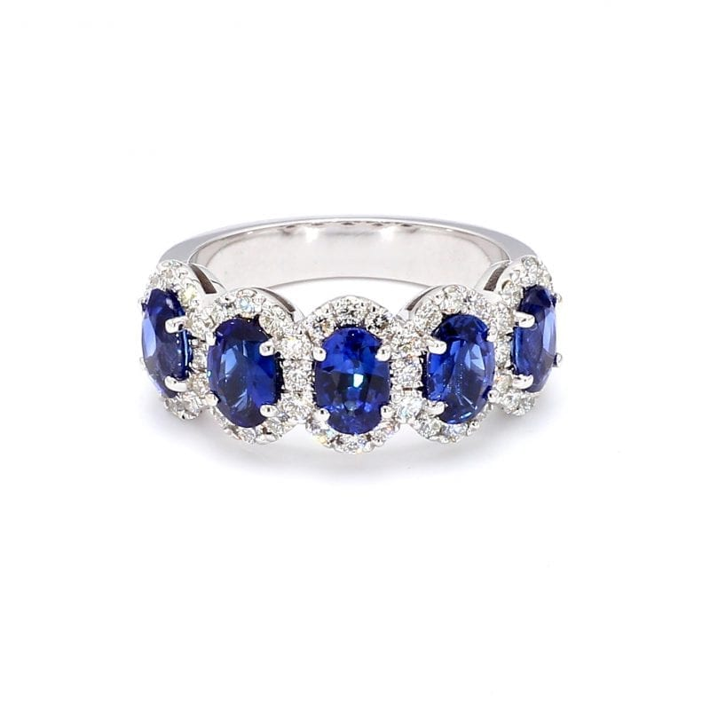 Front view of ring. A row of five oval cut, blue sapphires are set along the front half of a simple white gold band with interlocking pave diamond halos.